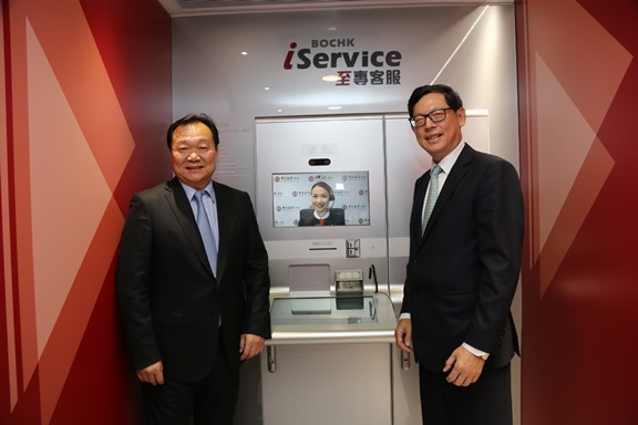 Mr Yue Yi, Vice Chairman and Chief Executive of the BOCHK (left) introduces the bank's newly launched video teller machine services to Mr Norman Chan, Chief Executive of the HKMA (right).