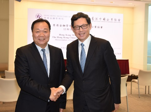 Mr Norman Chan, Chief Executive of the HKMA [right] greets Mr Yue Yi, Chairman of the HKCEA [left].
