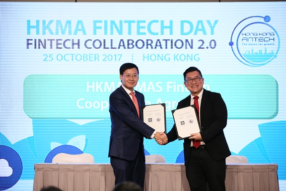 Mr Shu-pui Li, Executive Director of the HKMA (left) and Mr Roy Teo, Head, Financial Centre Development Department of MAS (right) exchange the Co-operation Agreement, which was signed between heads of the two organisations, at the HKMA Fintech Day today.