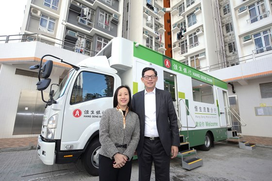 Ms. Louisa Cheang (left), Vice-Chairman and Chief Executive of Hang Seng Bank, and Mr. Norman Chan (right), Chief Executive of the HKMA, take a photo together in front of the mobile branch.
