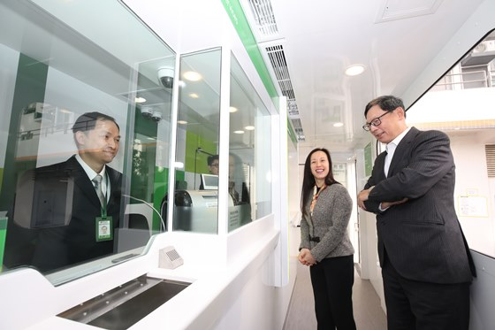 Ms. Louisa Cheang (middle), Vice-Chairman and Chief Executive of Hang Seng Bank, introduces the design and services of the mobile branch to Mr. Norman Chan (right), Chief Executive of the HKMA.
