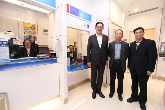 Mr. Chen Xiaozhou (second from right), Chairman of Nanyang Commercial Bank, Mr. Fang Hongguang (first from right), Vice Chairman and Chief Executive of Nanyang Commercial Bank, and Mr. Norman Chan (third from right), Chief Executive of the HKMA, take a photo together in front of the bank counter which facilitates access by people who are physically challenged.