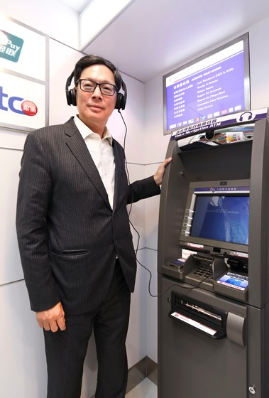 Mr. Norman Chan, Chief Executive of the HKMA, tries out the voice navigation ATM.
