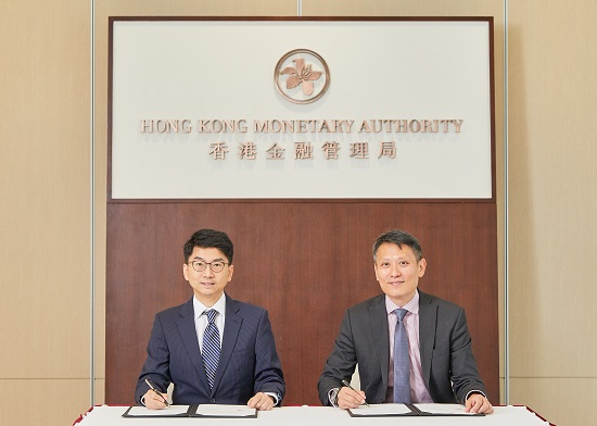 Mr Nelson Chow, Chief Fintech Officer of the HKMA (left), and Mr Richard Teng, Chief Executive Officer of the FSRA, sign and exchange the Co-operation Agreement in Hong Kong today (26 June 2018).
